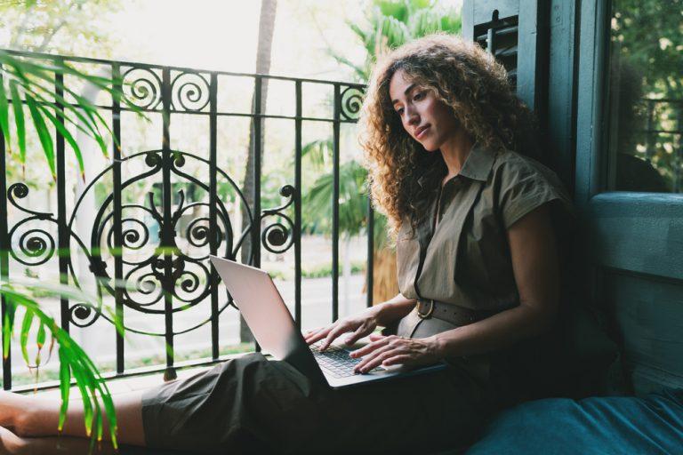Chica con su ordenado portátil trabajando en su web profesional