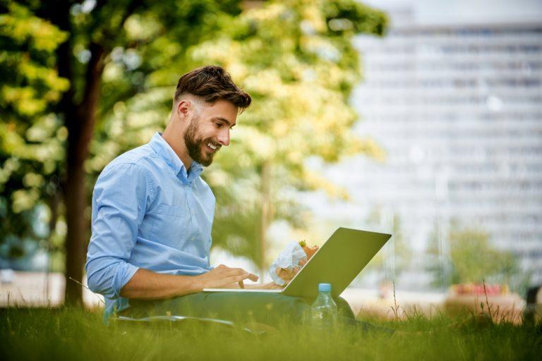 Chico empleando su ordenador portátil para trabajar en su web profesional en el exterior